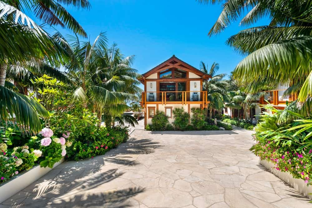 This is the front of the house showing the wide driveway flanked by lush flowering shrubs and tropical trees that provide a colorful background for the house. Image courtesy of Toptenrealestatedeals.com.