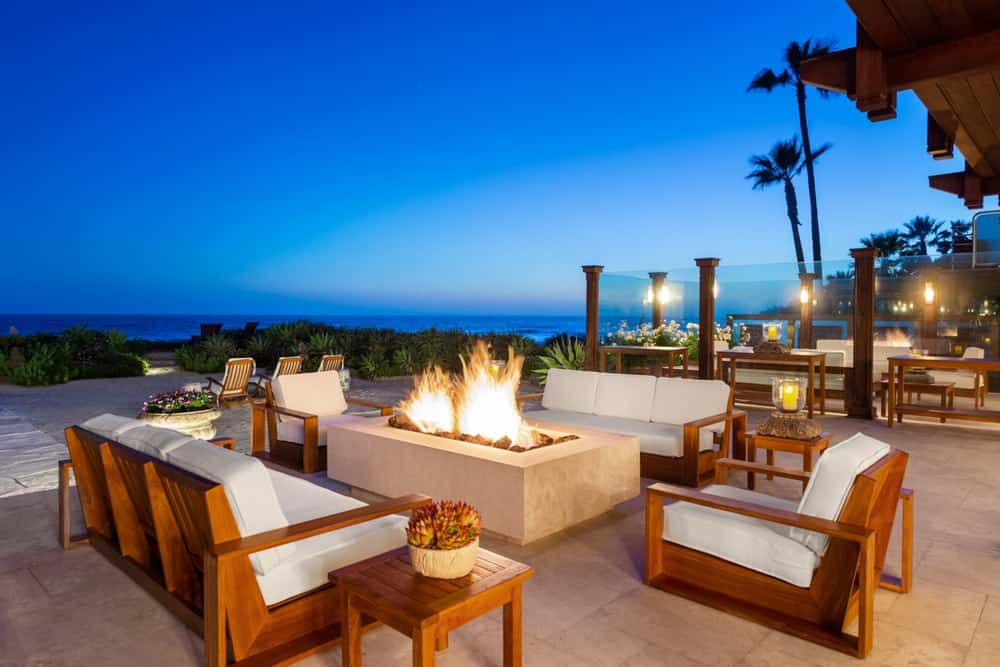 This is a nighttime view of the outdoor patio with wooden sofas and armchairs surrounding a warm fire pit. Image courtesy of Toptenrealestatedeals.com.