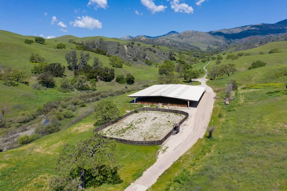 This is an aerial view of the riding arena and equestrian center of the property. These are then surrounded by various green landscape. Image courtesy of Toptenrealestatedeals.com.