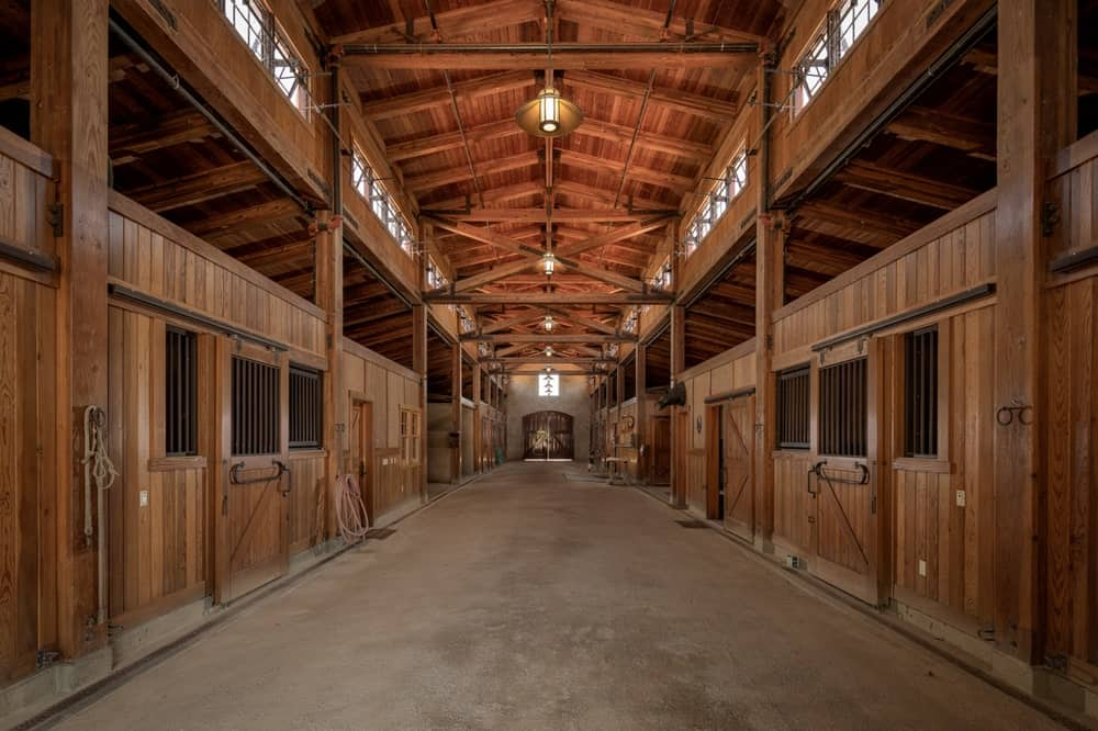 This is the interior of the large barn and equestrian center with multiple stalls for a number of horses under a large wooden cathedral ceiling. Image courtesy of Toptenrealestatedeals.com.