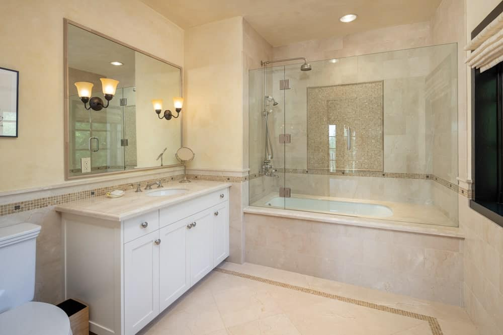 This other bathroom has a consistent beige tone to its walls, floor and vanity with a large mirror adorned by mounted sconces. Next to this is the bathtub on the far side. Image courtesy of Toptenrealestatedeals.com.