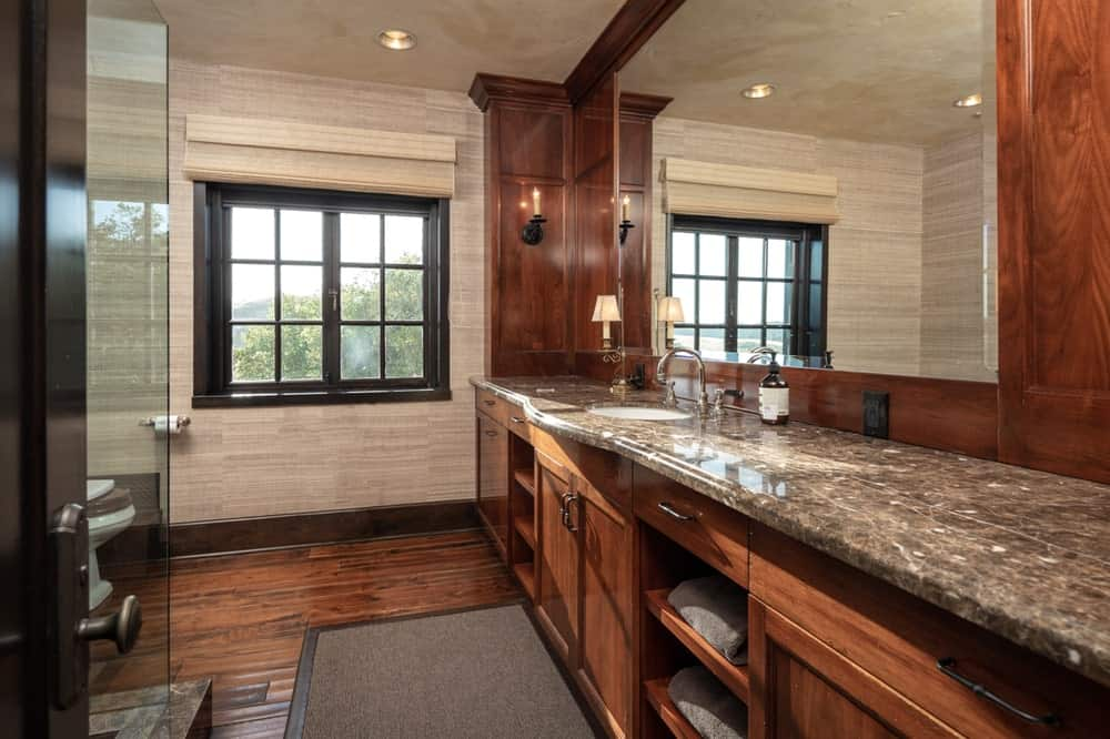 This other bathroom has a large two-sink vanity with dark wooden cabinetry and shelves that matches the hardwood flooring that contrast the beige walls. Image courtesy of Toptenrealestatedeals.com.