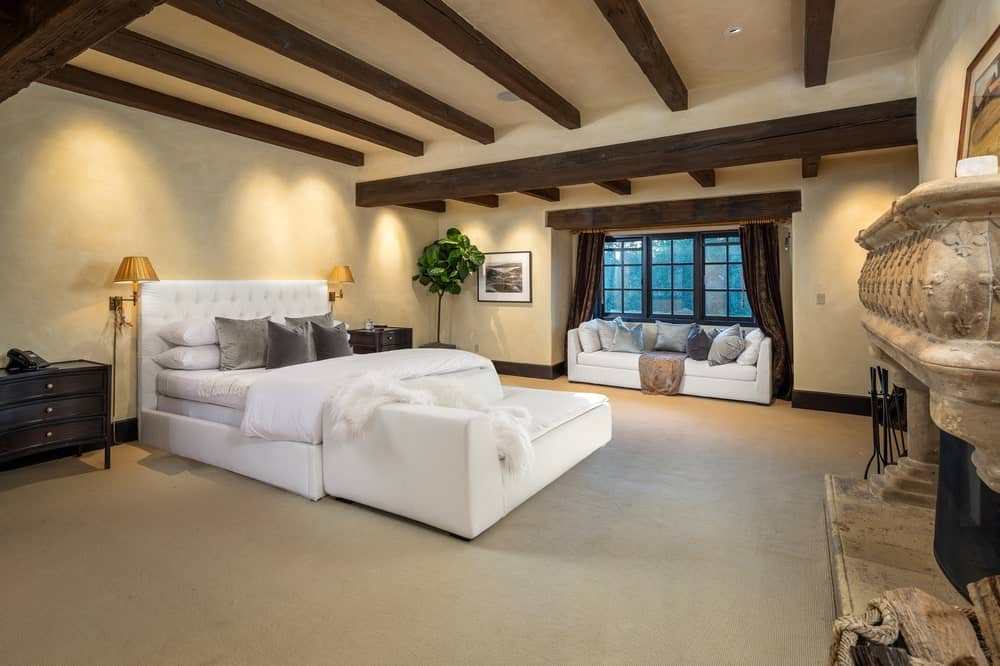 This is the bedroom with a beamed ceiling. The bed is paired well with a daybed at the foot and a sofa under the window for a reading nook. Image courtesy of Toptenrealestatedeals.com.