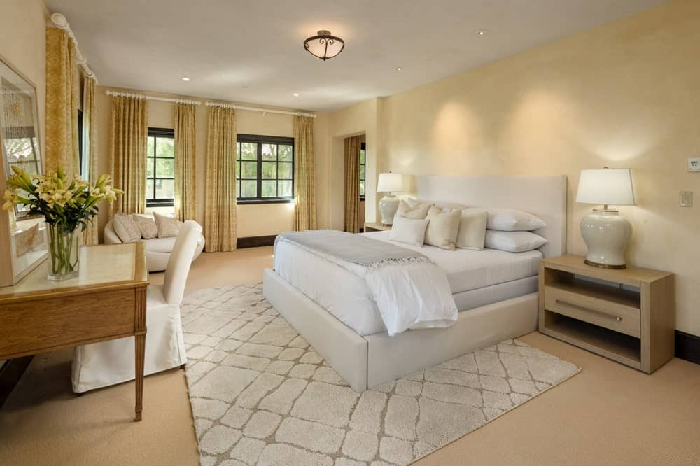 The beige walls of this bedroom matches with the beige carpeting on the floor complemented by the patterned area rug underneath the bed. Image courtesy of Toptenrealestatedeals.com.