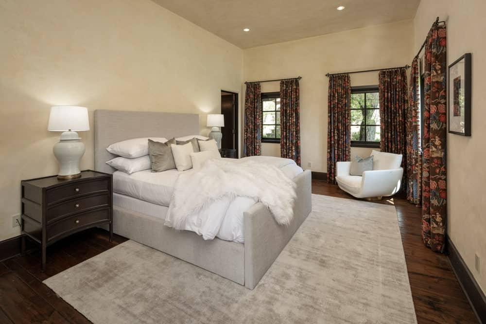 This bedroom has a beige cushioned bed with a large headboard flanked by lamps on dark bedside drawers. Image courtesy of Toptenrealestatedeals.com.