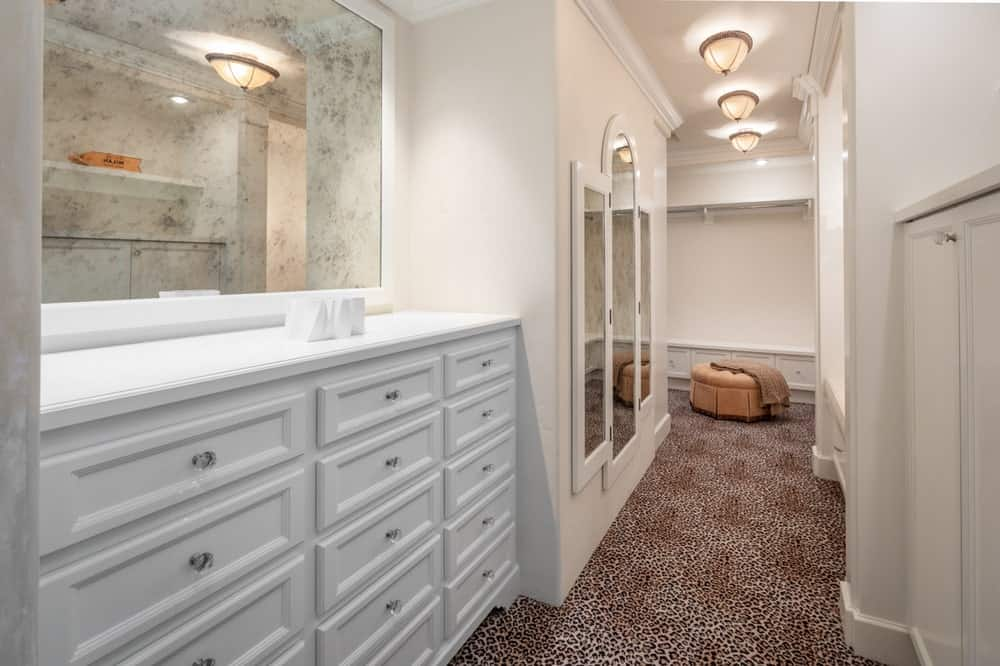 This is a look at the walk-in closet of the house with multiple white drawers beneath a marge mirror and a long hallway leading to the cabinets. Image courtesy of Toptenrealestatedeals.com.