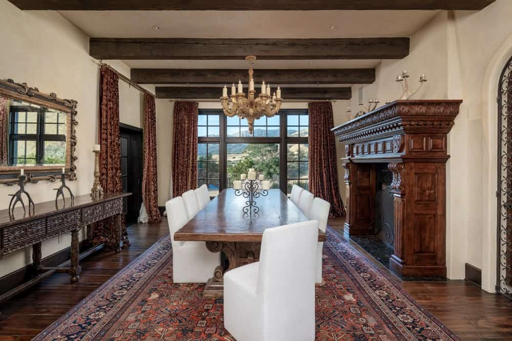This is the large formal dining room with a large wooden dining table surrounded by white cushioned chairs warmed by the fireplace with a alrge wooden mantle on the side. Image courtesy of Toptenrealestatedeals.com.