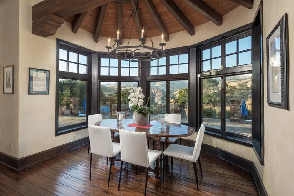 This is the breakfast nook just a few steps from the kitchen. It has a small dining table surrounded by white cushioned chairs brightened by the surrounding tall windows. Image courtesy of Toptenrealestatedeals.com.