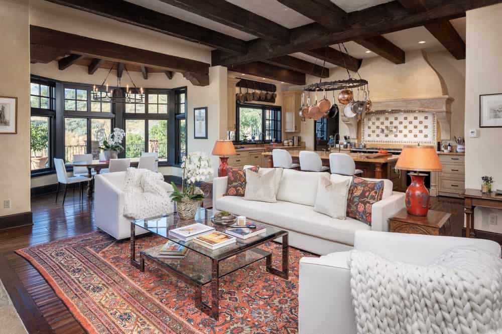 This is the family room area just a few steps from the kitchen. It has white sofas and armchairs that contrast the dark hardwood flooring and area rug. Image courtesy of Toptenrealestatedeals.com.