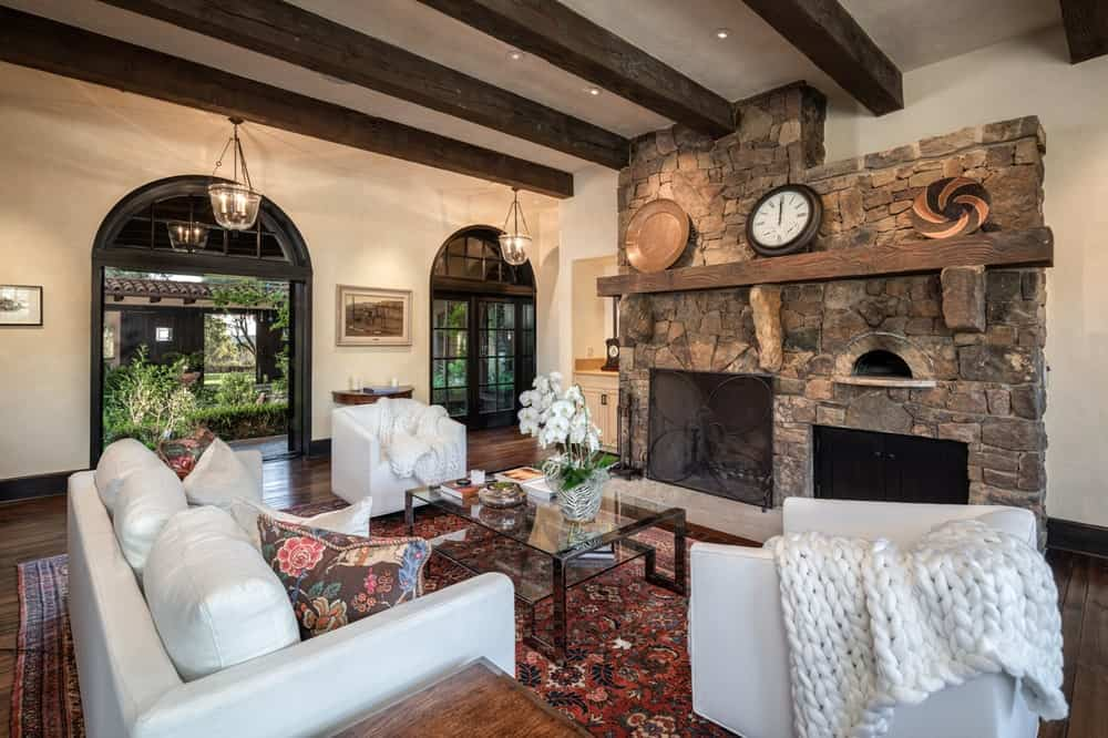 This view of the family room showcases the stone fireplace across from the white sofa set and glass-top coffee table. Image courtesy of Toptenrealestatedeals.com.