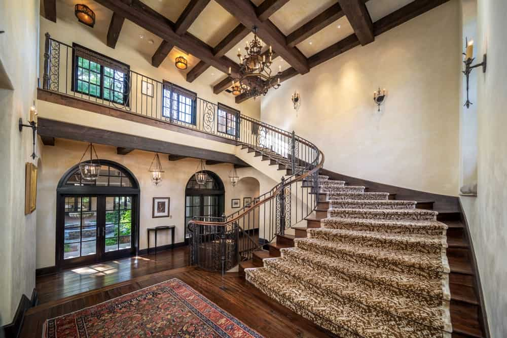 Upon entry of the house, you are welcomed by this foyer that has a tall beamed ceiling with a chandelier. The beams of the ceiling matches the staircase, hardwood flooring and the frames of the glass doors. Image courtesy of Toptenrealestatedeals.com.