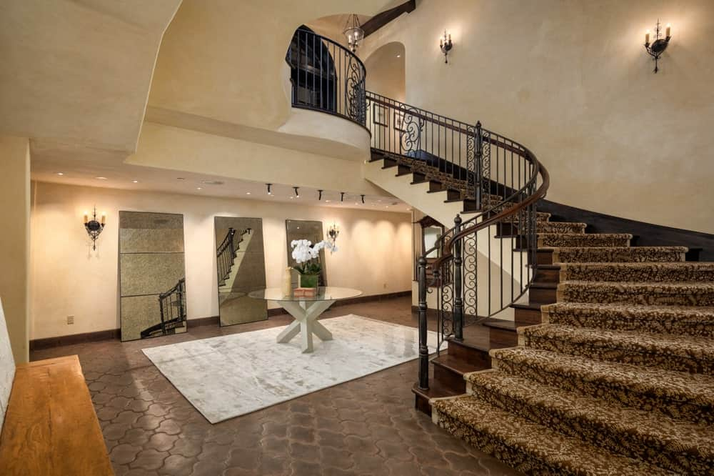 This is the foyer of the basement area with a large curved staircase with dark steps and carpeting to match the dark earthy tiles of the floor contrasted by the area rug and beige walls. Image courtesy of Toptenrealestatedeals.com.