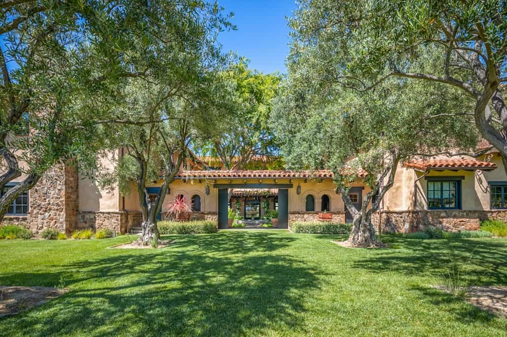 This is a look at the front of the main house with a large archway leading to the courtyard. This also shows the earthy tone of the exteriors complemented by the trees and grass. Image courtesy of Toptenrealestatedeals.com.