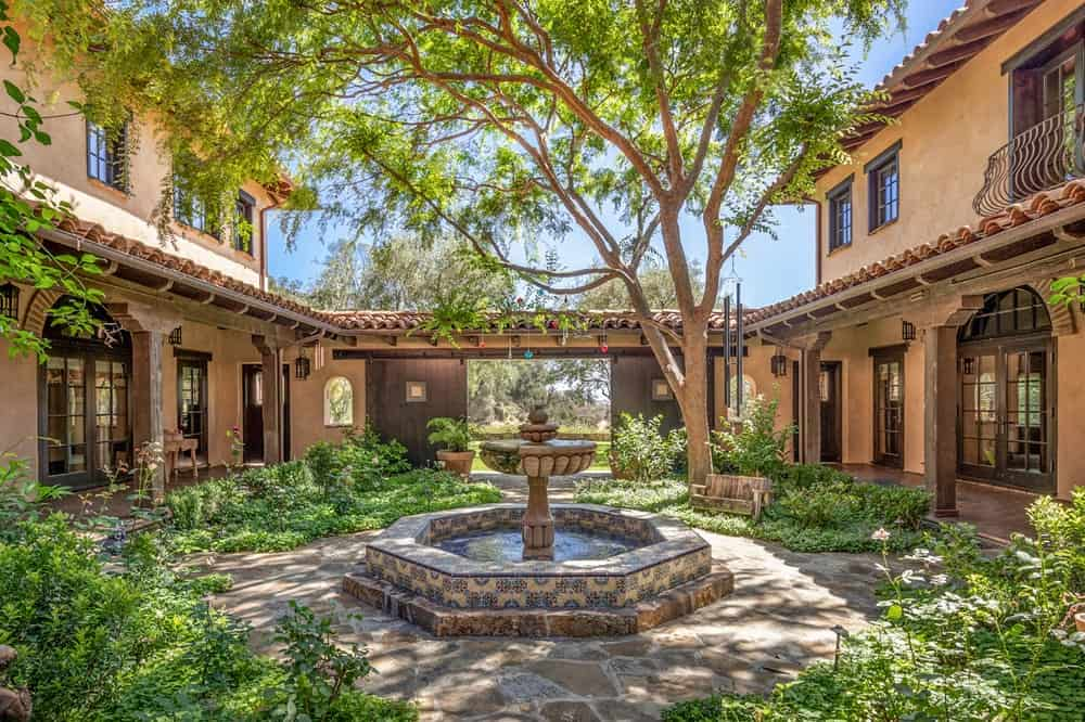 This is a look at the front courtyard of the main house with a large fountain in the middle surrounded by concrete walkways, shrubs and tall trees. Image courtesy of Toptenrealestatedeals.com.