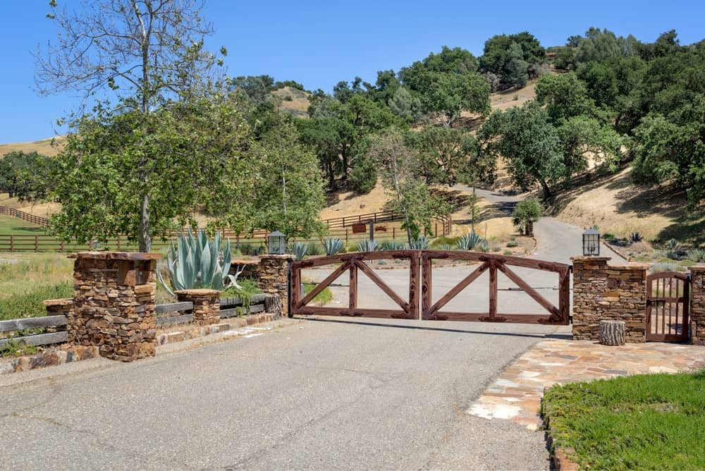 This is a look at the gate of the ranch with small stone pillars and a wide concrete driveway. Image courtesy of Toptenrealestatedeals.com.