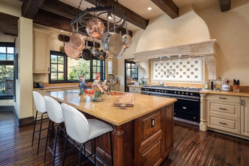 This is the kitchen with a large kitchen island that matches the tone of the hardwood flooring and the beams of the ceiling. These are then complemented by the earthy beige tone of the walls. Image courtesy of Toptenrealestatedeals.com.