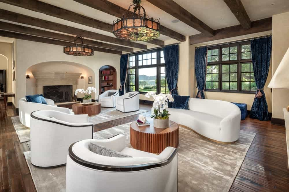 This is the spacious living room with sets of white sofas and armchairs under a beamed ceiling with a couple of drum lighting over the two wooden coffee tables. Image courtesy of Toptenrealestatedeals.com.