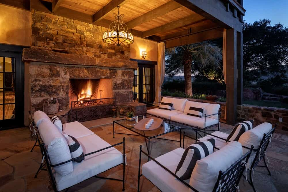 This is the covered patio at the back of the house with a large stone fireplace to warm the set of wrought-iron sofas and armchairs with cushions. Image courtesy of Toptenrealestatedeals.com.