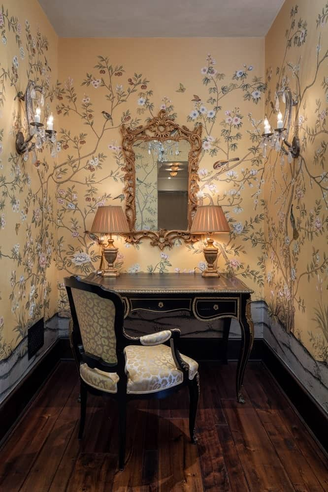 This corner of the house is the study with a single wooden chair facing a wooden desk with drawers and a couple of table lamps on top. These are then surrounded by floral wallpaper. Image courtesy of Toptenrealestatedeals.com.