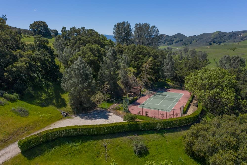 This is an aerial view of the tennis court of the property that is surrounded by thick foliage of tall trees and shrubs. Image courtesy of Toptenrealestatedeals.com.