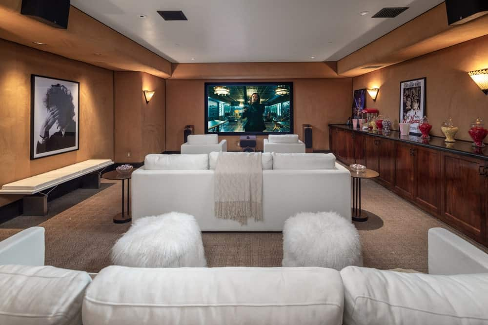 This is the home theater room with a large screen at the far end of the room across from rows of white sofas that stand out against the earthy walls. Image courtesy of Toptenrealestatedeals.com.
