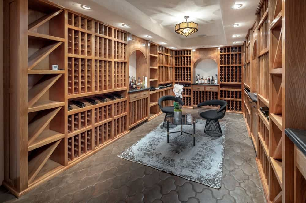 This is the wine cellar that can hold hundreds of wine bottles in its wooden built-in structures lining the walls that surround the two armchairs and small round table. Image courtesy of Toptenrealestatedeals.com.