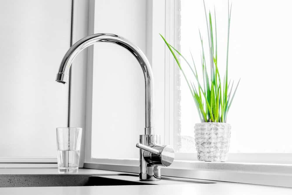 A stainless steel single handle faucet at a kitchen sink.