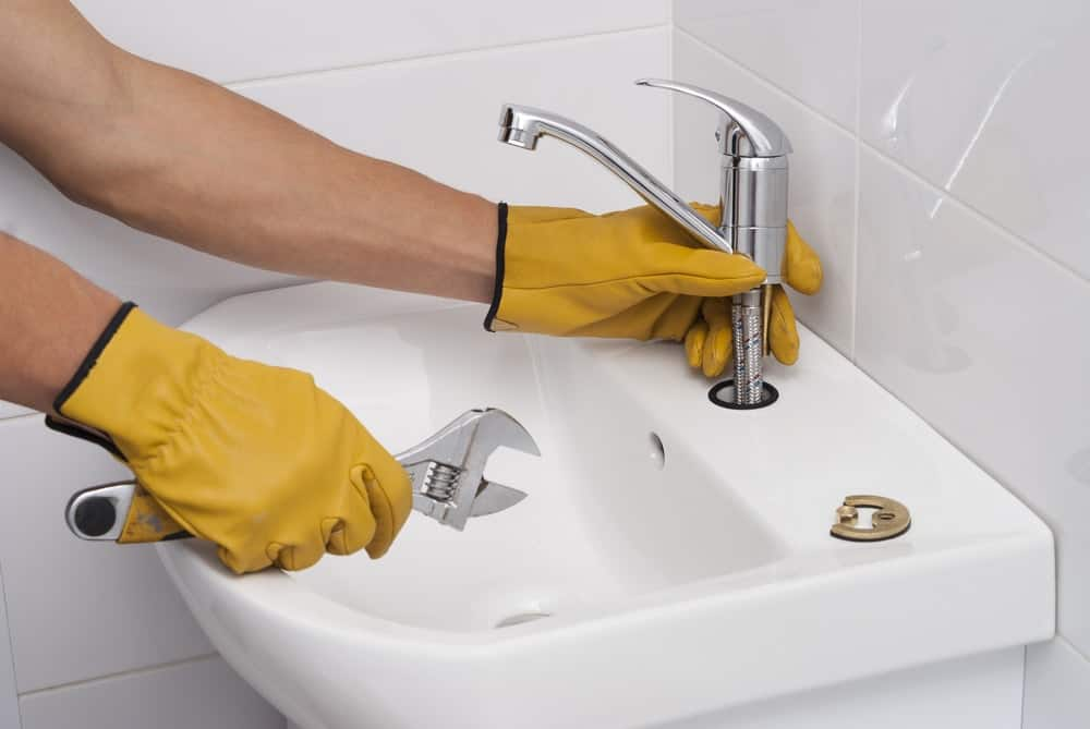 A close look at a plumber installing a single handle faucet at a bathroom sink.