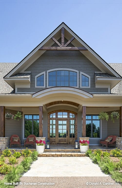 Home entry showing the arched front door and the covered porch lined with rustic columns.