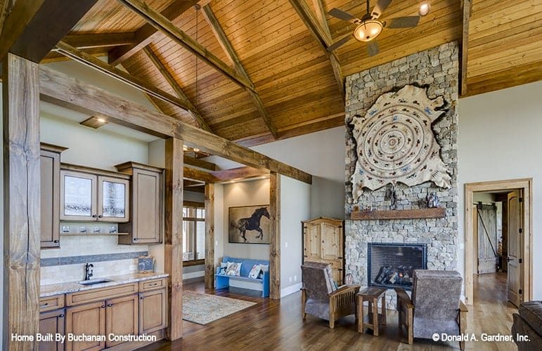The foyer leads to the great room where you'll find a wet bar and a fireplace complemented by cushioned chairs.