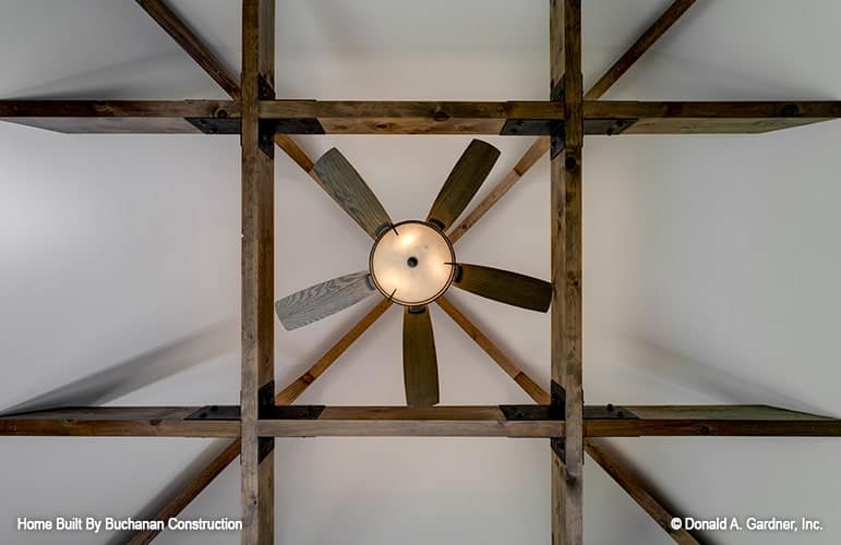 A closeup look at the vaulted ceiling framed with rustic beams.