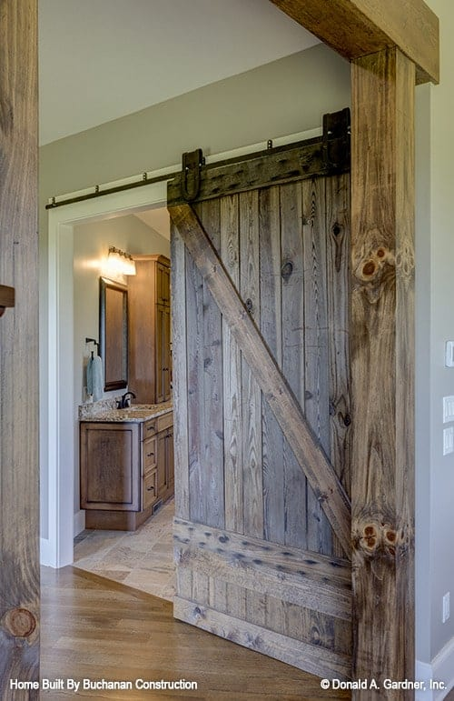 An open doorway with a sliding barn door leading to the primary bathroom.