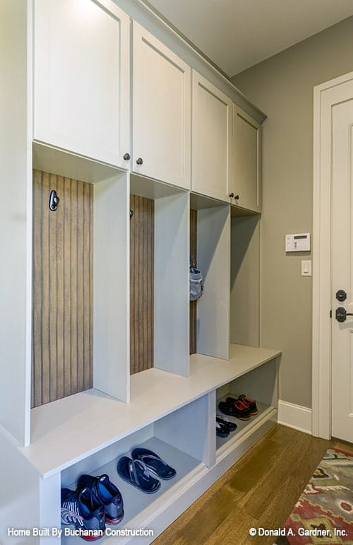 The mudroom is filled with overhang cabinets, coat hooks, and a storage bench.
