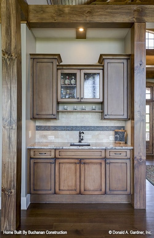 Wet bar with natural wood cabinets, tiled backsplash, and an undermount sink.