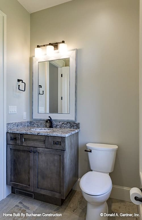The powder room has a toilet and a granite top vanity paired with a framed mirror.