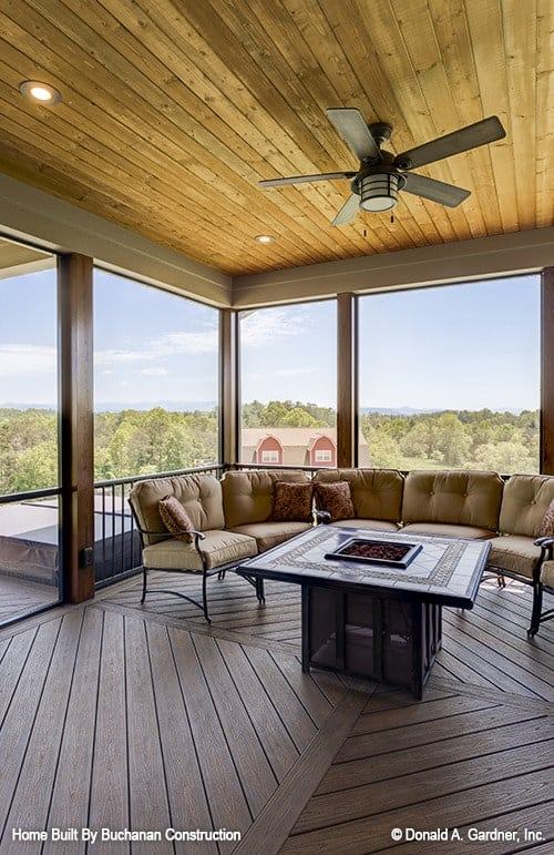 Screened porch with a cushioned metal sofa, a fire pit coffee table, and a panoramic view of the expansive surrounding.