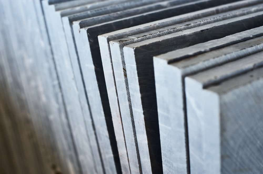 A close look at a stack of thick granite slabs on display.