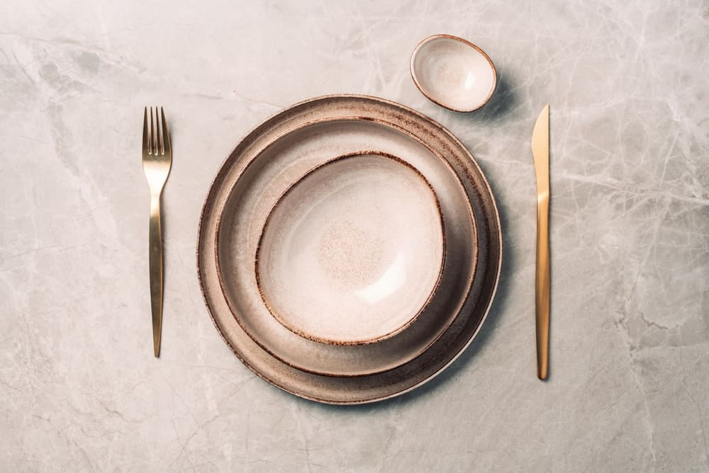 A top view of a stoneware plate setup with copper spoon and fork.