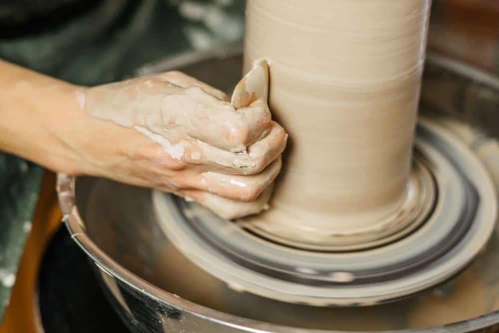 A potter making pottery on a potter's wheel.