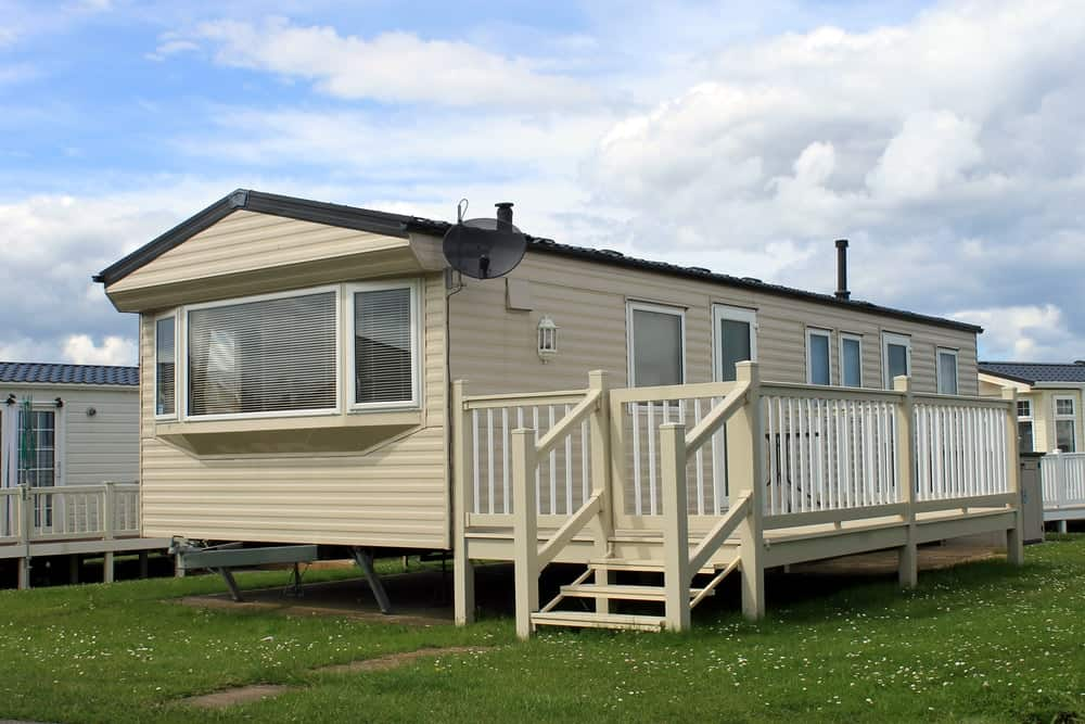A look at a trailer home inside a trailer ark with a beige tone.