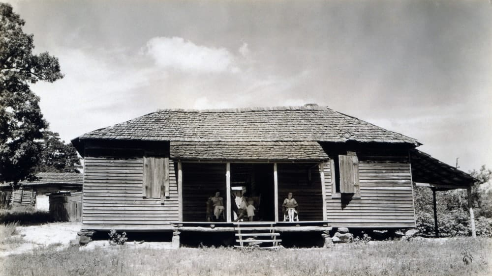 A 1936 photo of an old cotton farm home made of wood.