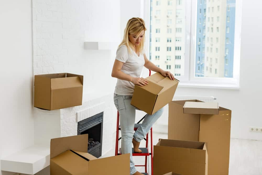 A woman unboxing her things in a new apartment.