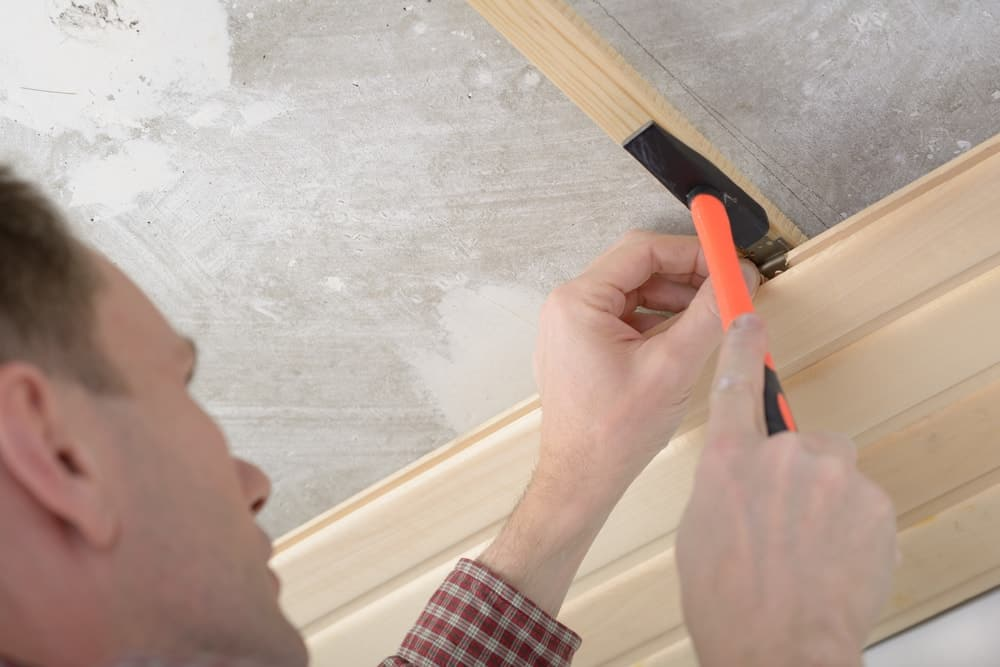 A man installing wood paneling onto the ceiling.