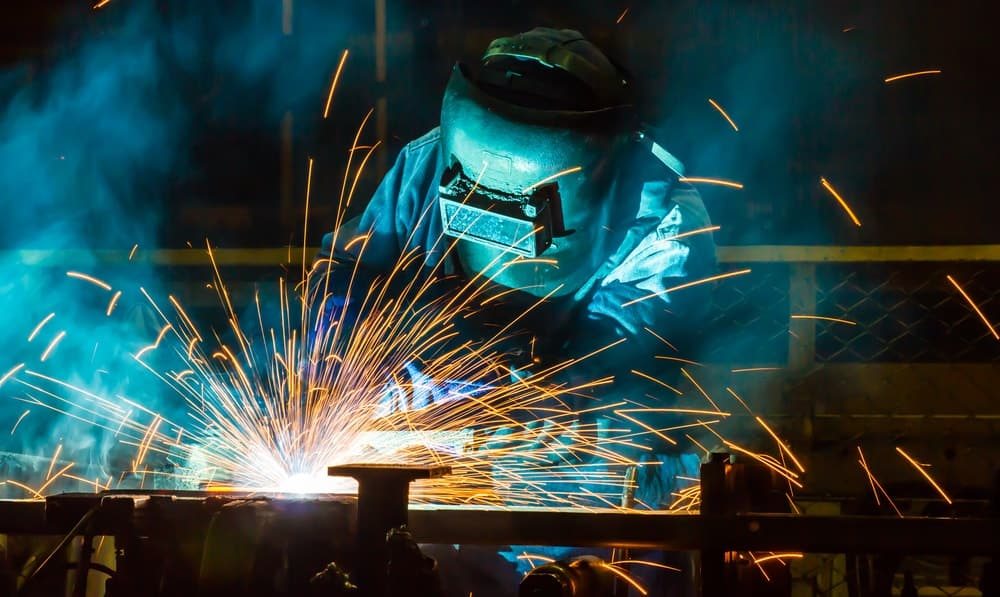 A factory worker welding steel parts together.