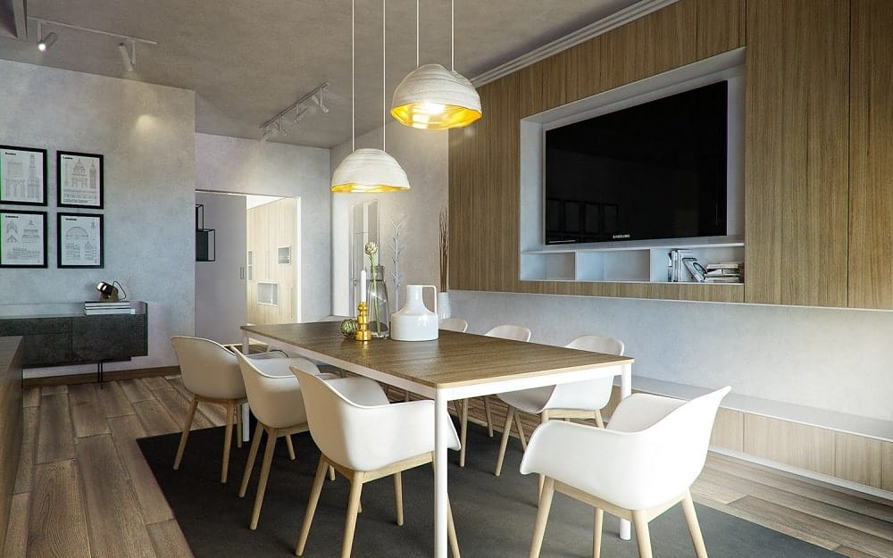 This is the dining room that has a rectangular dining table surrounded by beige chairs across from a large TV and topped with a couple of pendant lights.