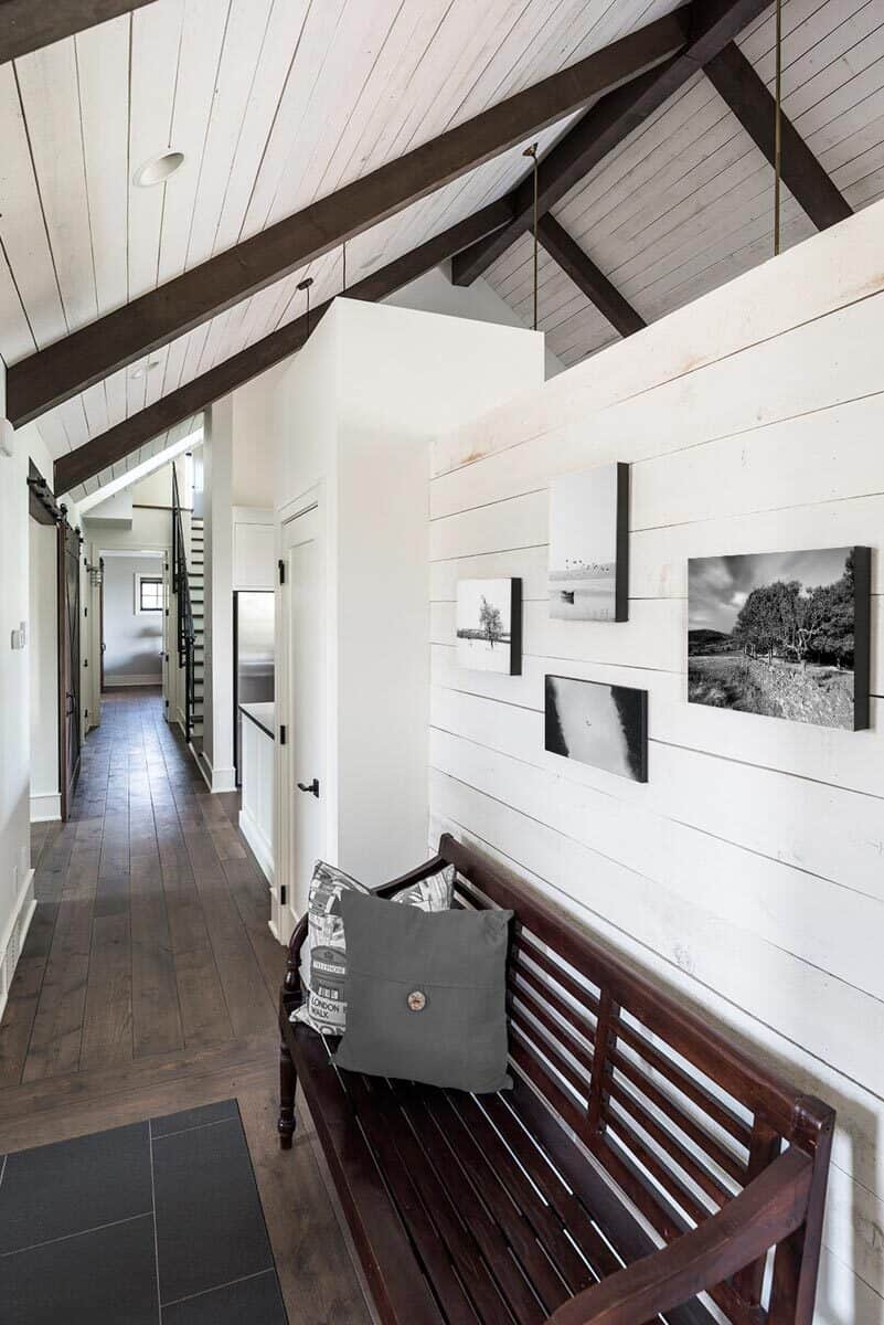 Foyer with a wooden bench and white shiplap walls adorned with black and white artworks.