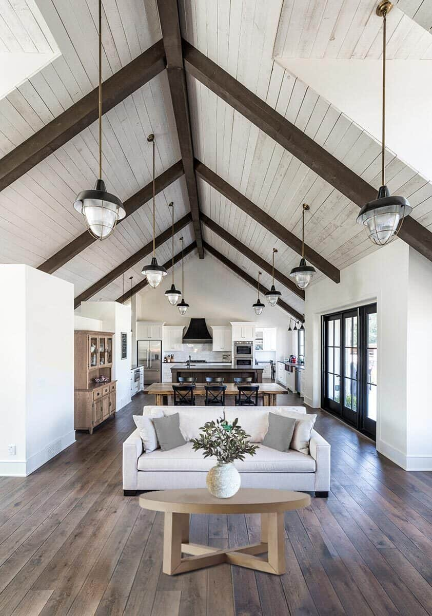 The living room features a white sofa paired with a round coffee table. It opens to the dining area and kitchen.