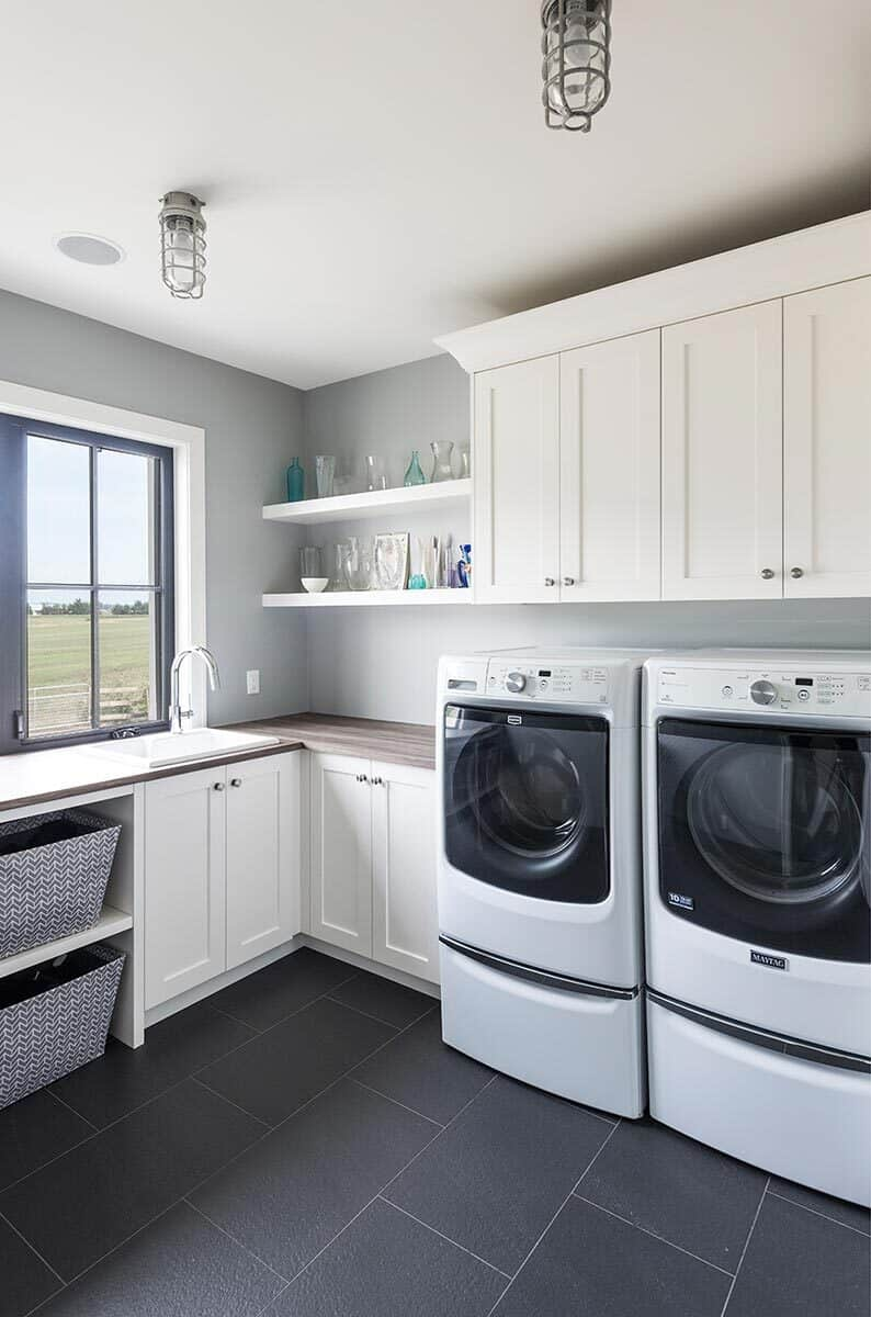 Laundry room with white cabinets, built-in shelves, white front-load appliances, and a porcelain sink.