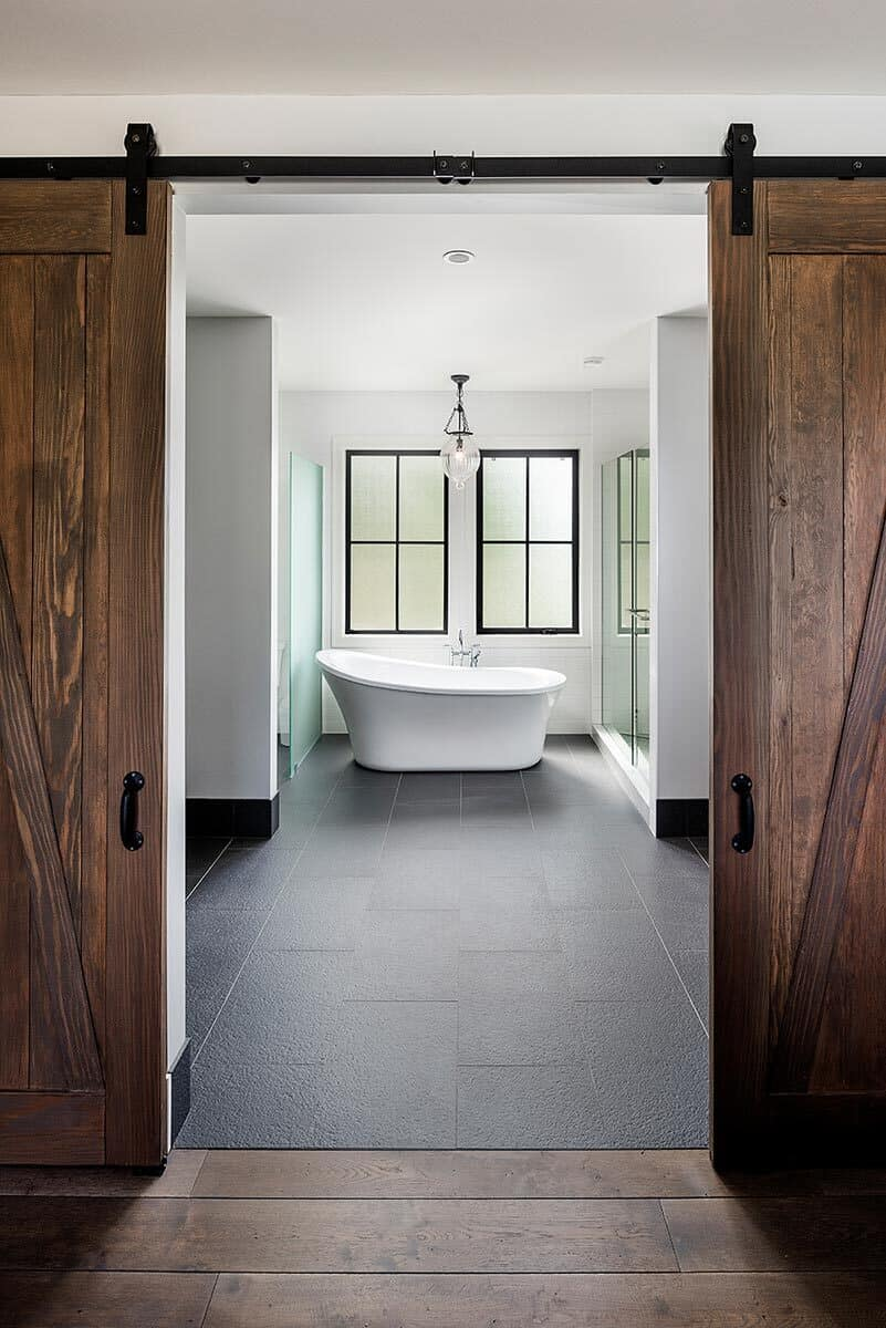 A sliding barn door opens to the primary bathroom. It has a freestanding tub flanked by the toilet room and a walk-in shower.