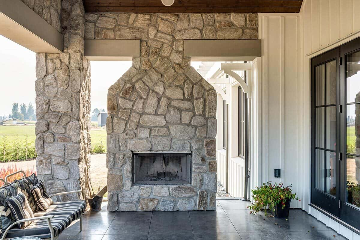 Rear porch with cushioned seats and a large stone fireplace that matches the columns.